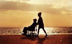 osoba na wózku inwalidzkim na tle zachodzącego słońca prowadzona przez kobietę